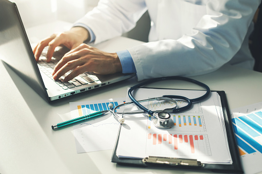 Doctor Working With Medical Statistics And Financial Reports In Office — стоковые фотографии и другие картинки Анализировать