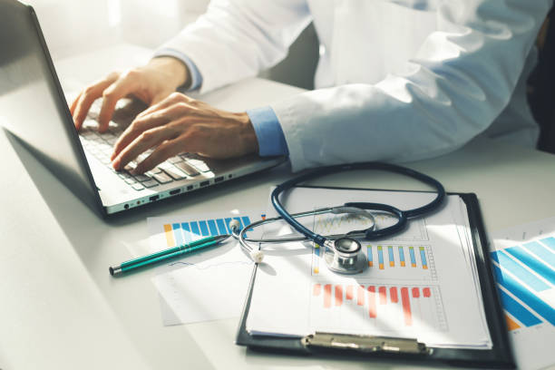doctor working with medical statistics and financial reports in office - healthcare and medicine stock pictures, royalty-free photos & images
