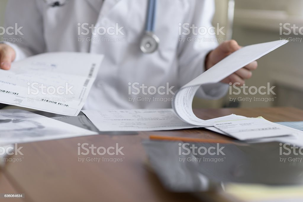 Doctor working with test results stock photo