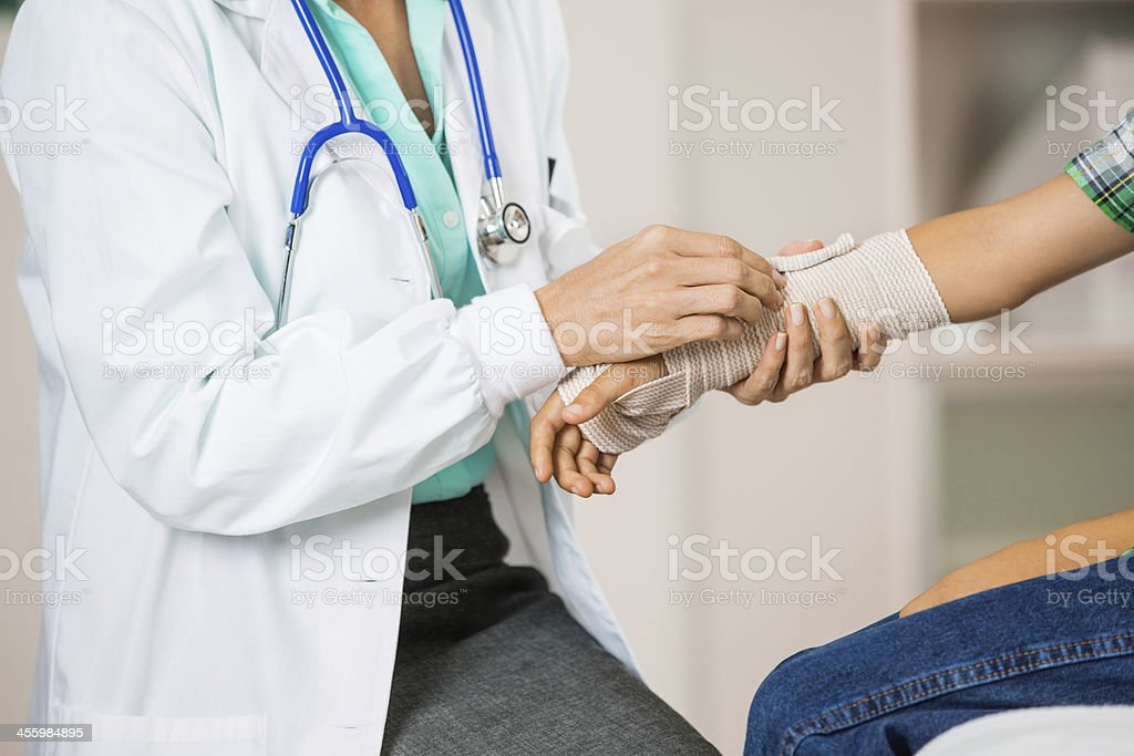 Doctor wrapping boy's injured wrist in office stock photo