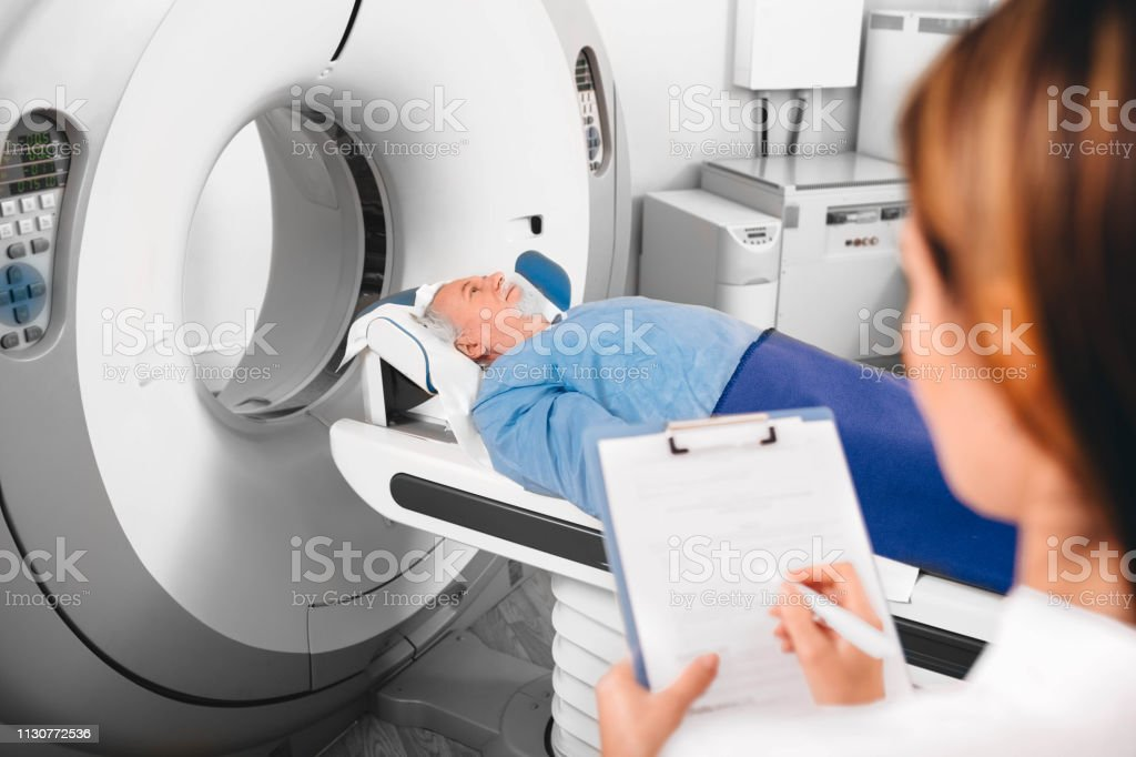 doctor write into medical chart after CT Scan in hospital.CT Scan...