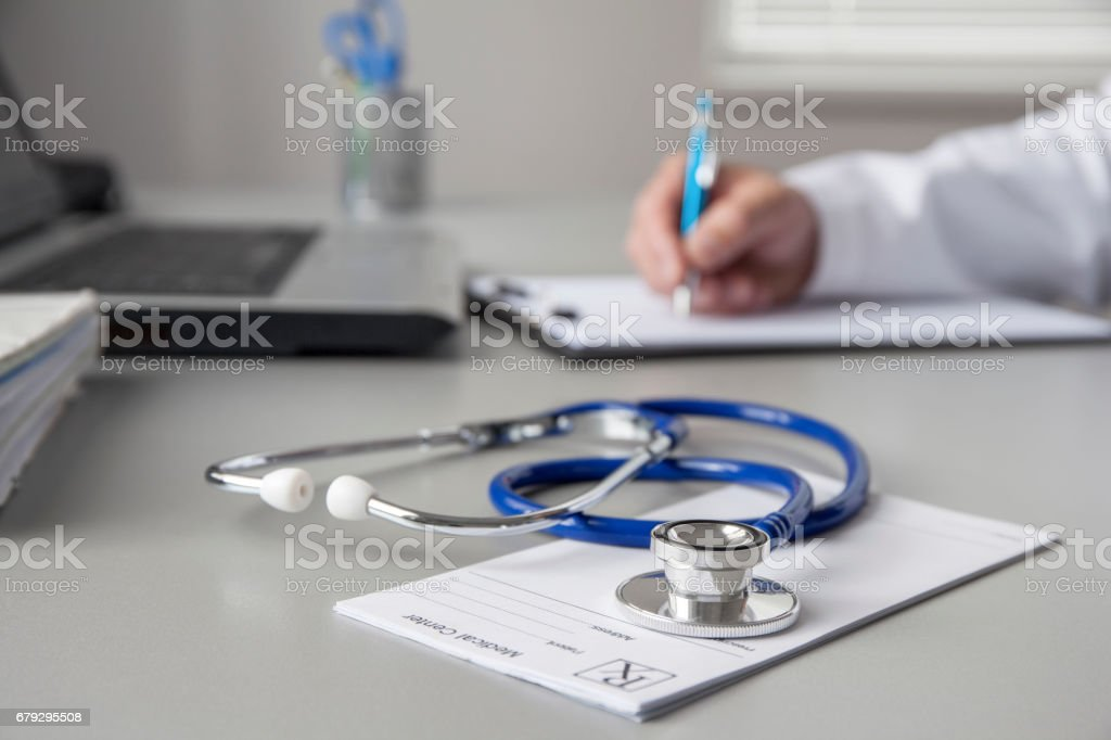 Doctor Writing A Document In The Consulting Room stock photo