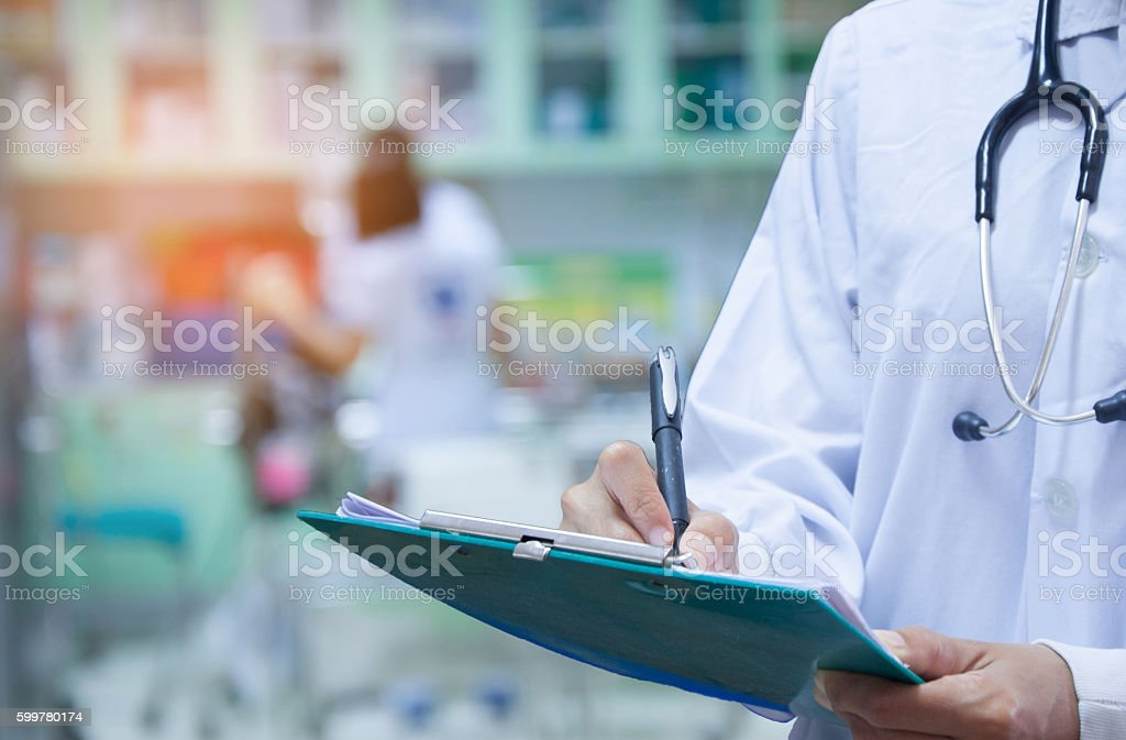 Doctor writing a medical prescription in hospital stock photo
