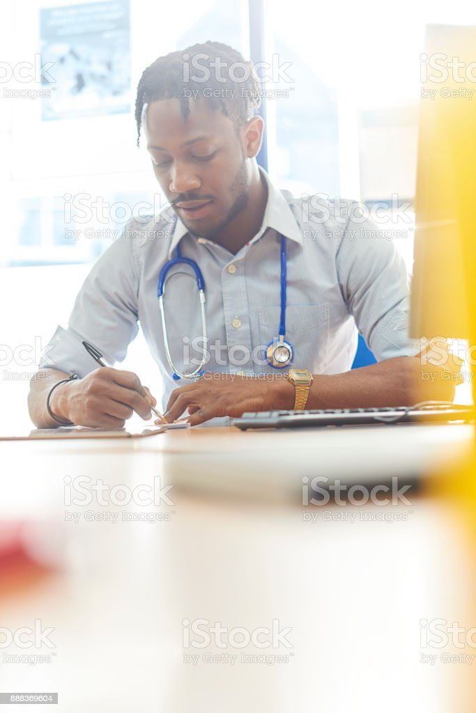 Junior doctor at his desk in his office performing various tasks