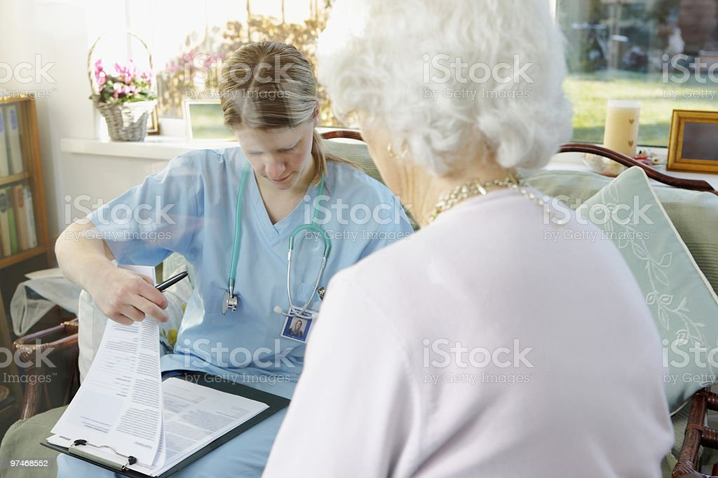 doctor writing medical report for senior woman in care home royalty-free stock photo