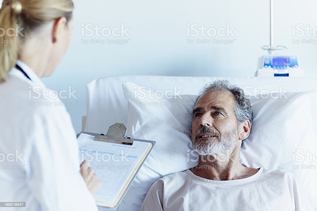 Doctor writing notes while talking to male patient stock photo