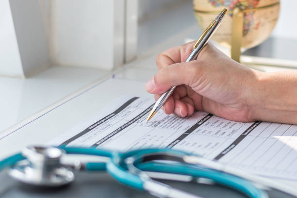 doctor writing on medical health care record, patients discharge, or prescription form paperwork in hospital clinic office with physician's stethoscope on desk - form document stock pictures, royalty-free photos & images