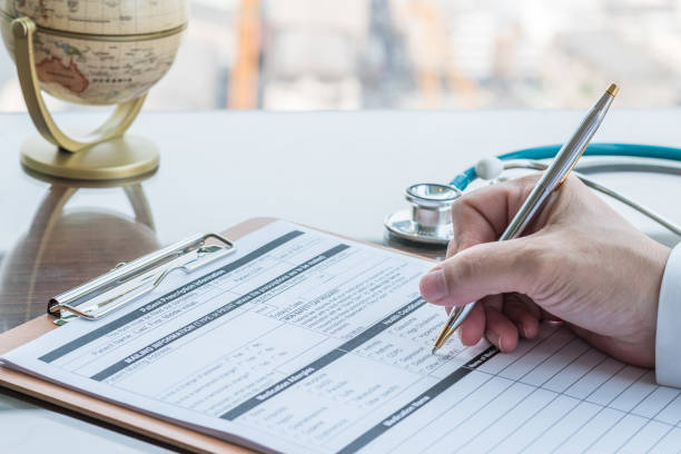 Doctor writing on medical health care record, patients discharge, or prescription form paperwork in hospital clinic stock photo