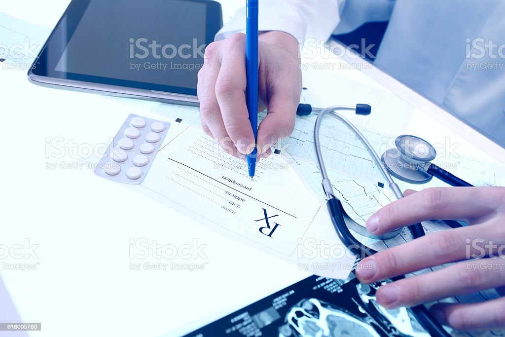 Doctor writing prescription in his office stock photo