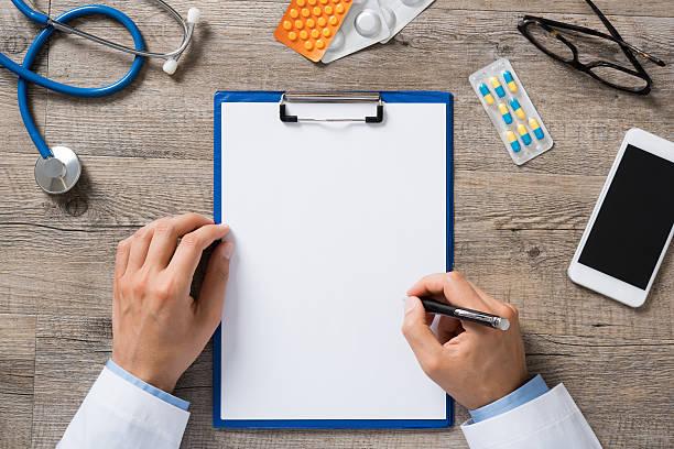 Doctor writing prescription stock photo