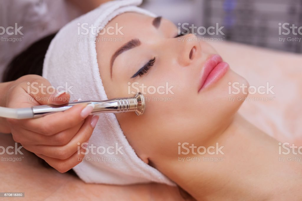 doctor-cosmetologist makes the procedure Microdermabrasion of the facial skin of a beautiful, young woman in a beauty salon stock photo