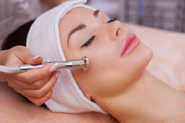 doctor-cosmetologist makes the procedure microdermabrasion of the facial skin of a beautiful, young woman in a beauty salon - beauty treatment stock photos and pictures