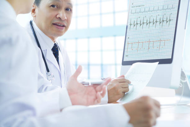 doctors analysing data in detail - cardiologist stock pictures, royalty-free photos & images
