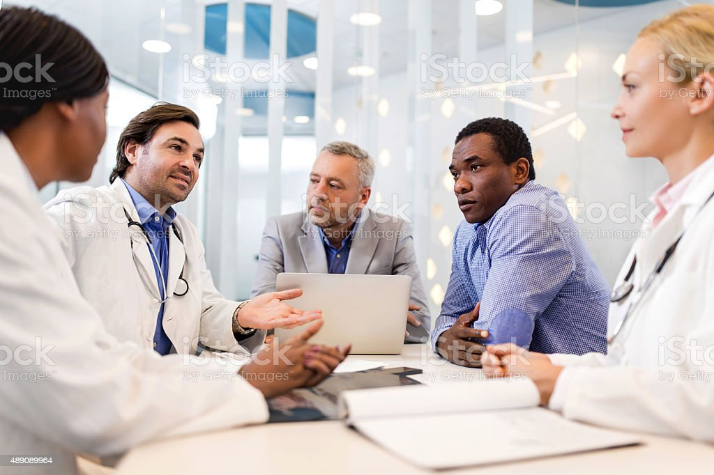 Doctors and business people communicating on a meeting. stock photo