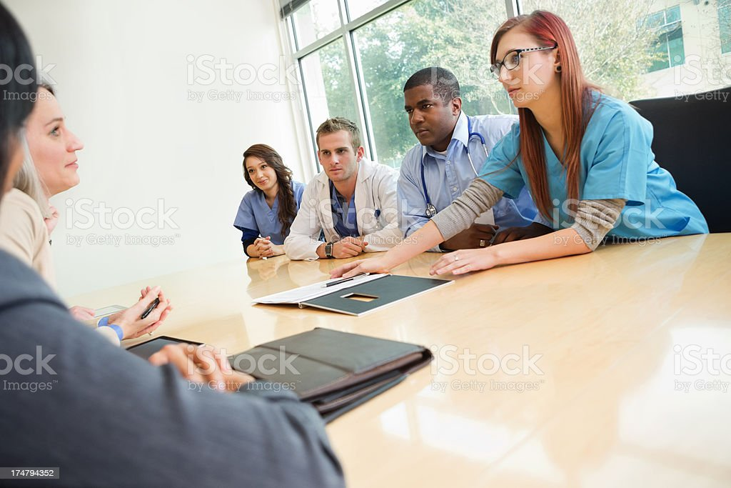 Doctors and interns having meeting with hospital's legal team royalty-free stock photo