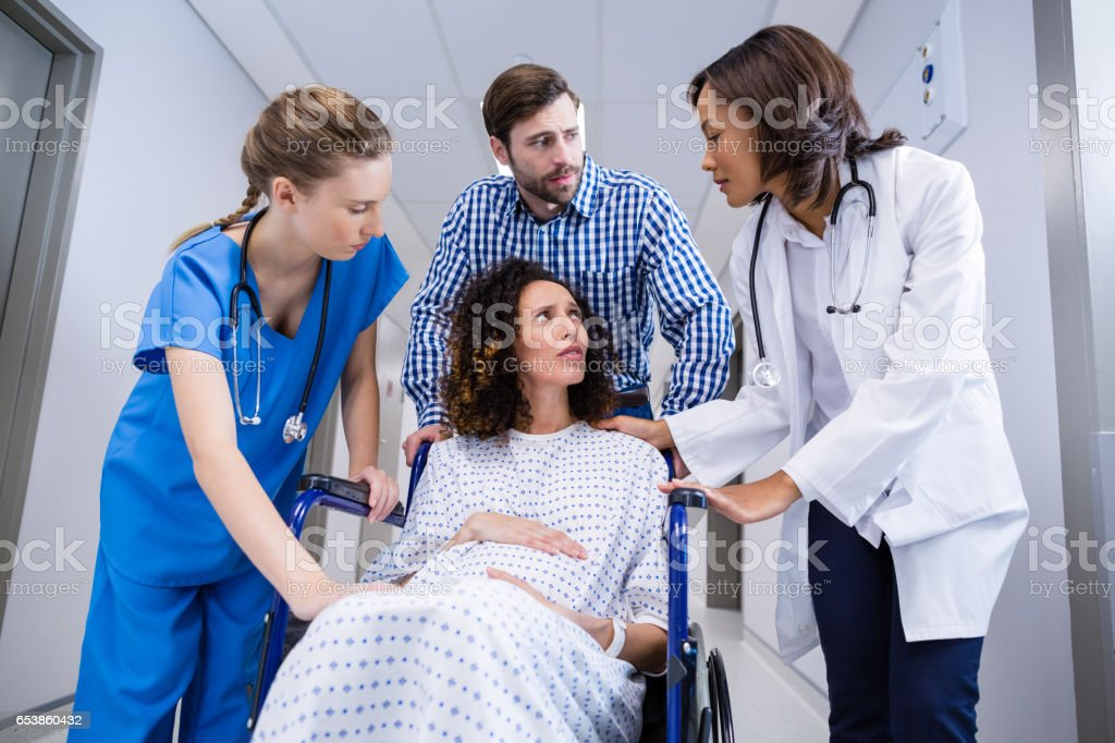 Doctors and man comforting pregnant woman in corridor stock photo