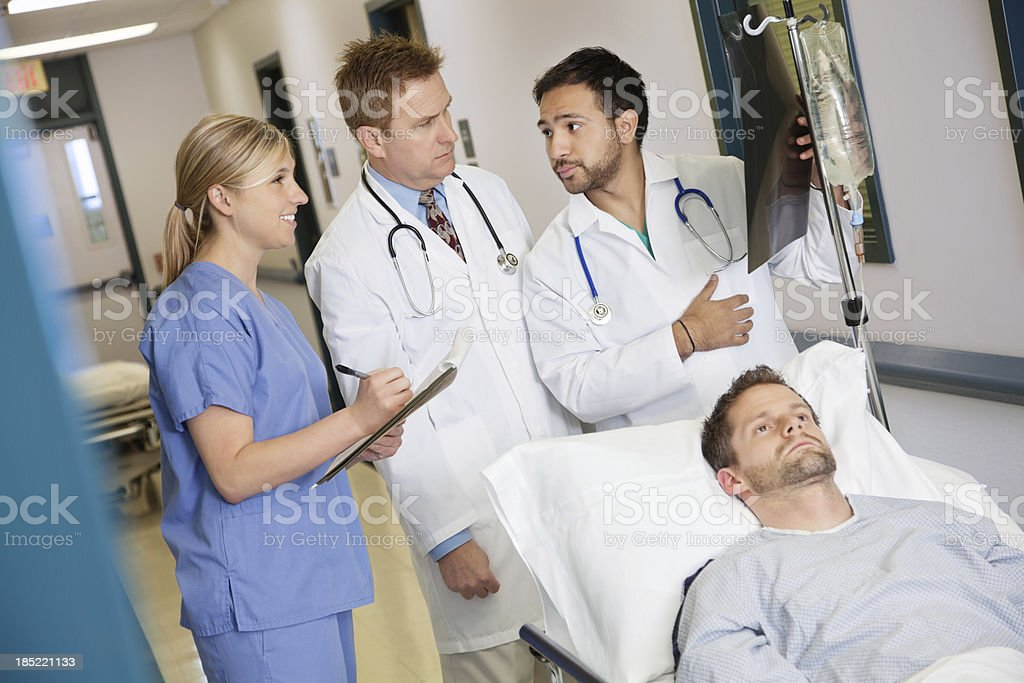Doctors and nurse discussing patient's x-ray in hospital royalty-free stock photo