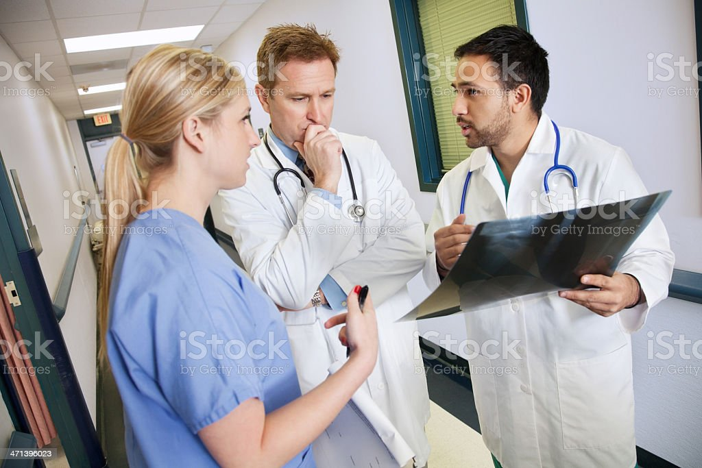 Doctors and nurse in serious conversation about patient's X-ray results royalty-free stock photo