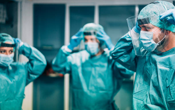 Doctors and nurse preparing to work in hospital for surgical operation during coronavirus pandemic outbreak - Medical workers getting dressed inside clinic - Focus on right man eye stock photo