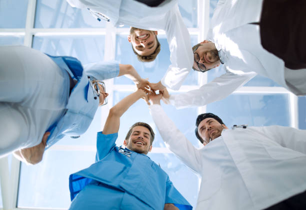 Doctors and nurses in a medical team stacking hands stock photo