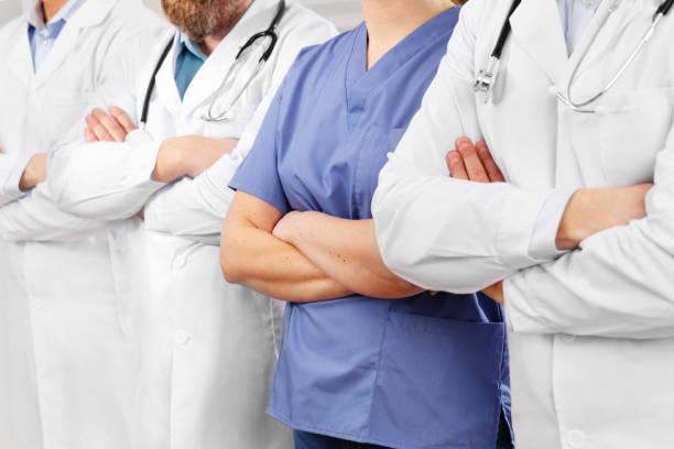Ärzte und Krankenschwestern im Gesundheitsteam mit Waffen, die hintereinander im Krankenhaus gekreuzt sind – Foto