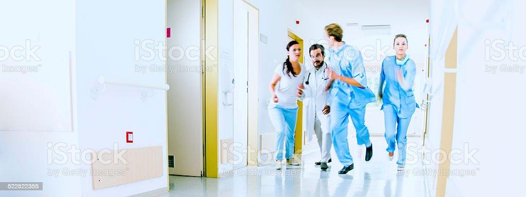 Doctors and Nurses Rush for Emergency in Hospital Corridor stock photo