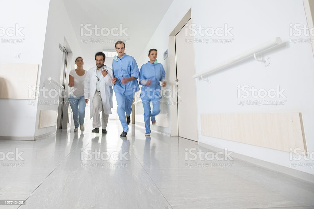 Blurred image of doctors running down a hospital corridor in an...