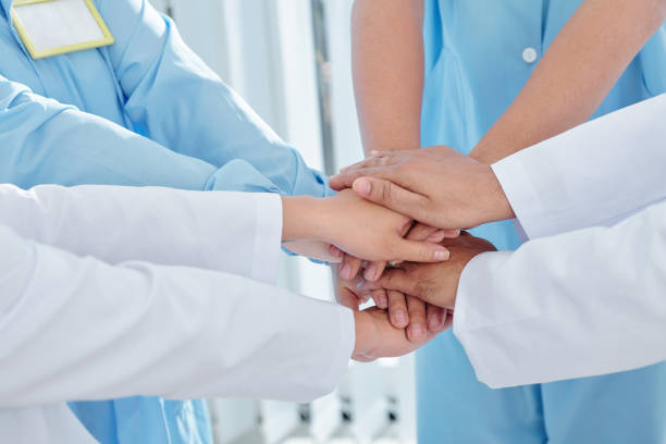 Doctors and nurses stacking hands stock photo