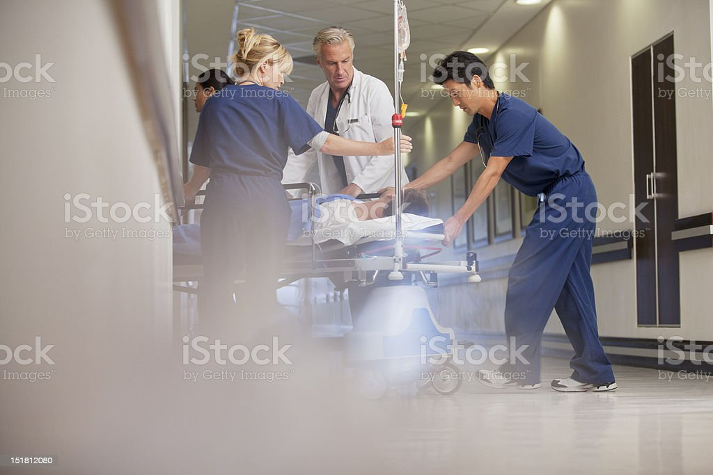 Doctors and nurses wheeling patient on gurney in hospital corridor stock photo