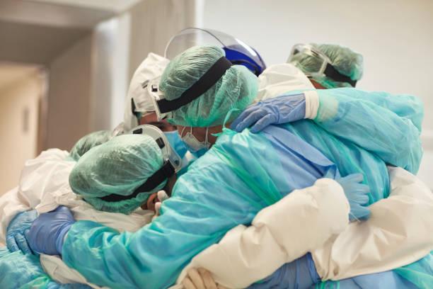 médecins et infirmières avec des bras autour de l'autre à l'appui - medecin covid photos et images de collection