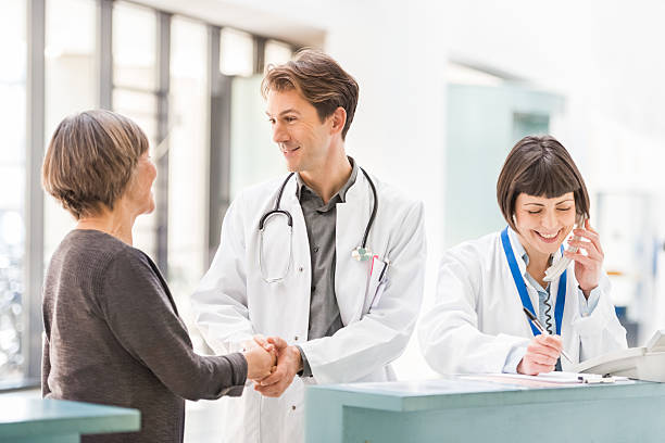 doctors and patient at reception desk - receptionist stock photos and pictures