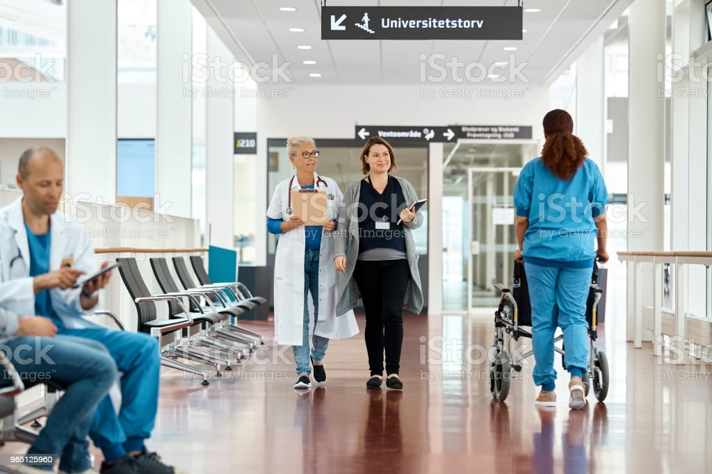 Female doctors looking away while walking while nurse is pushing...