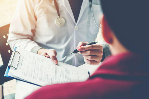 doctors and patients sit and talk. at the table near the window in the hospital. - form document stock pictures, royalty-free photos & images