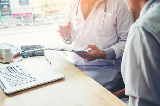 医師と患者に座るし、話します。病院の窓に近いテーブル。 - 診察室 ストックフォトと画像