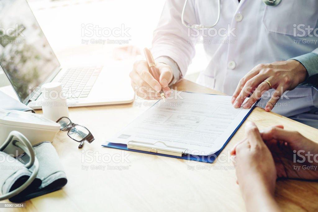 Médicos y pacientes sentarse y hablan con el paciente sobre la medicación. En la mesa cerca de la ventana en el hospital. - foto de stock