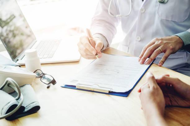 Ärzte und Patienten sitzen und sprechen Sie mit dem Patienten über Medikamente. Am Tisch neben dem Fenster im Krankenhaus. – Foto