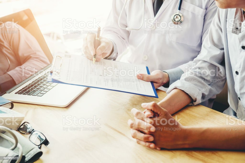 Doctors and patients sit and talk to the patient about medication. At...
