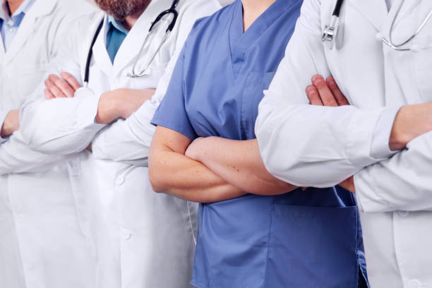 Doctors and surgeons in healthcare team with arms crossed in a row in hospital stock photo