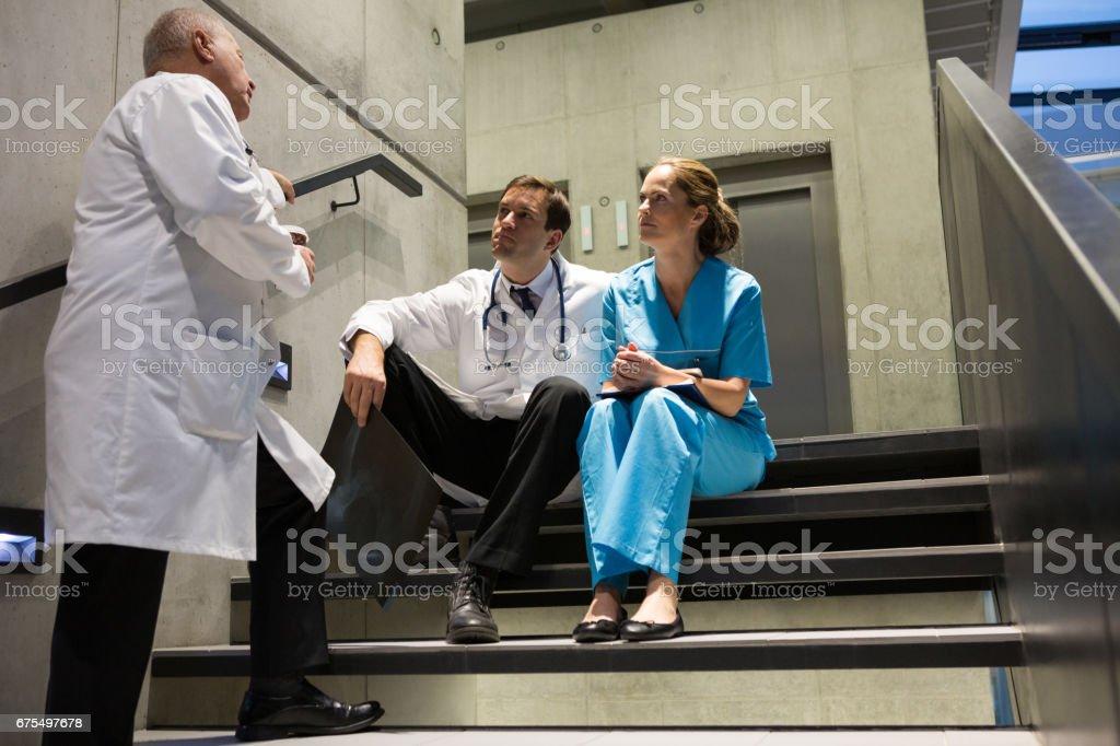 Médecins et chirurgiens interagissent entre eux sur l'escalier photo libre de droits