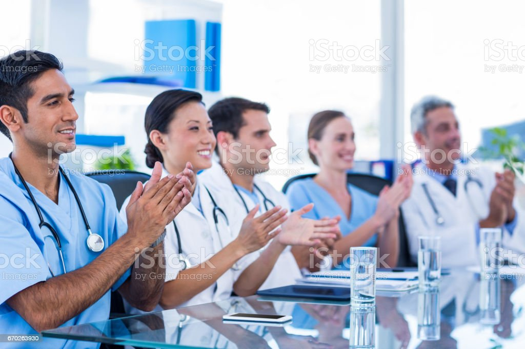 Doctors applauding while sitting at a table stock photo