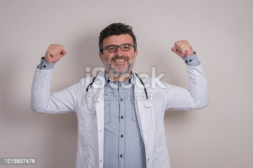 Handsome Hispanic doctor flexing his arm and showing his strength while wearing scrubs