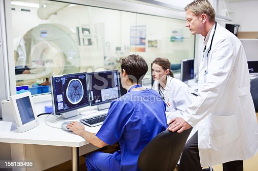 Patient, Doctor and medical technician at the computer tomography getting a scan