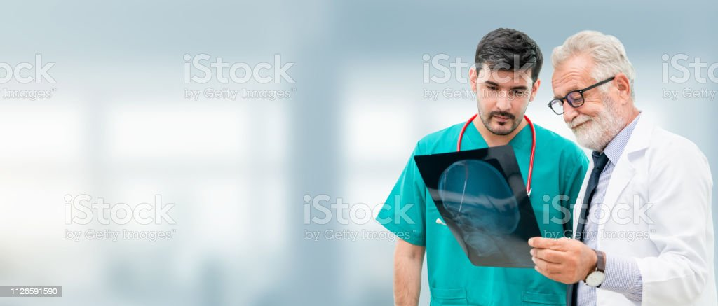 Doctors at hospital working with another doctor. stock photo