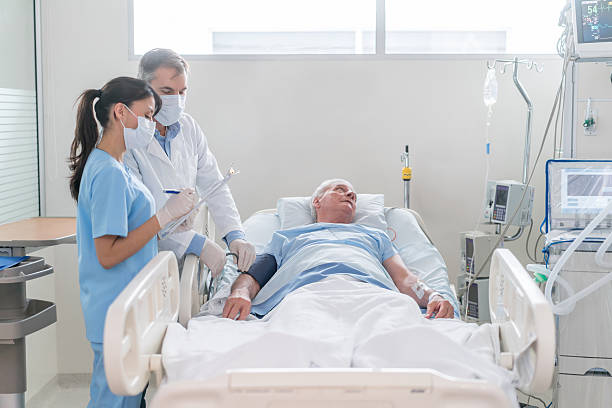 Doctors checking on patient at the ICU Doctors checking on a senior patient hospitalized at the ICU - healthcare and medicine intensive care unit stock pictures, royalty-free photos & images