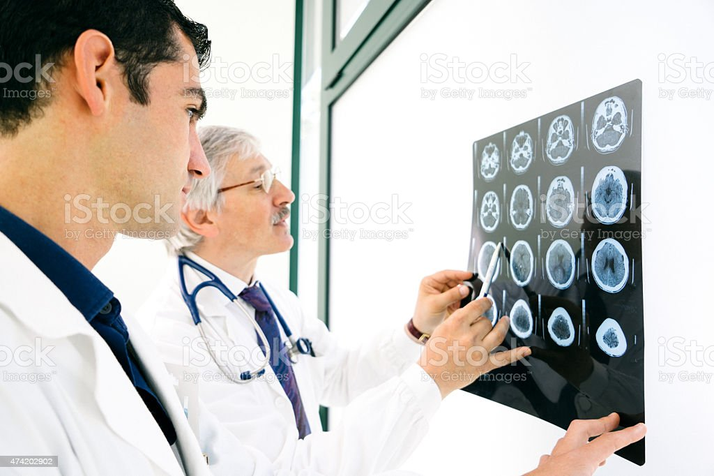Doctors Consult Over An MRI Scan Of The Brain Doctors consult over an MRI scan of the brain. 2015 Stock Photo