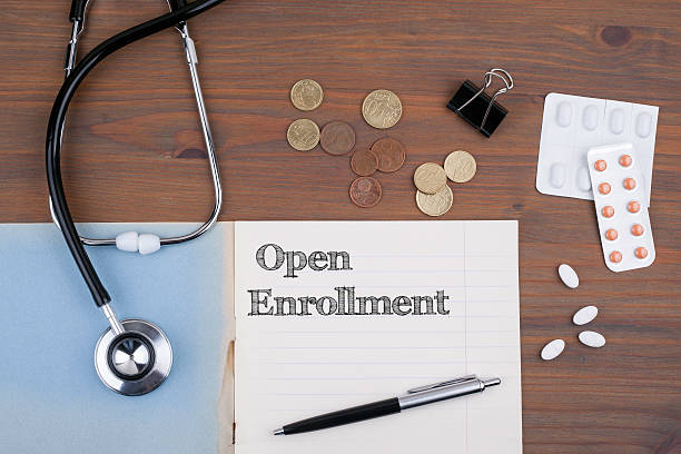 doctor's desk with notebook and text - open enrollment - open enrollment stock photos and pictures