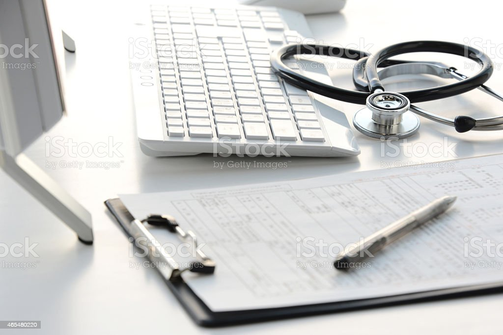 Doctor's desk with stethoscope, clipboard, and computer  stock photo