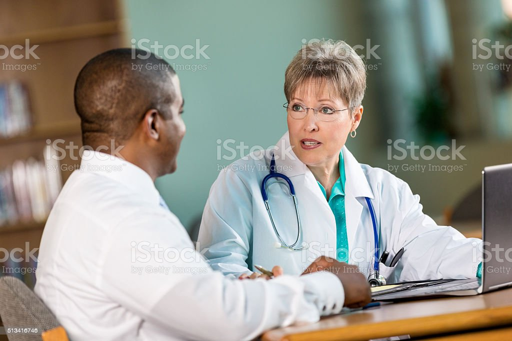Doctors discuss patient diagnois in staff meeting stock photo