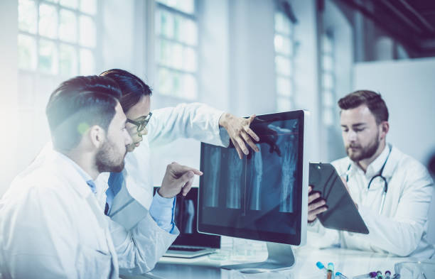 Doctors Discussing and Pointing at X-ray Images stock photo