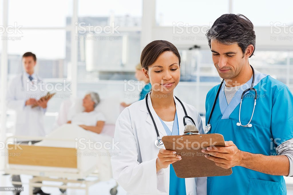 Doctors discussing reports with patient in background royalty-free stock photo